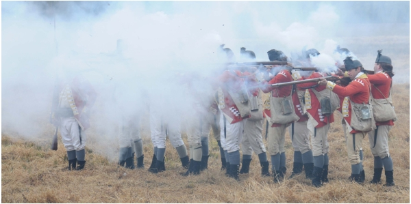 "Re-enactors and actors are engulfed in smoke after firing blank shots from their muskets during the filming of ""Making of an American Army."" (DOD photo by Sgt. 1st Class Raymond Piper)"
